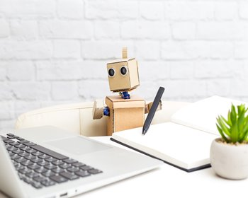 Cardboard robot looking at laptop while taking notes with a pen